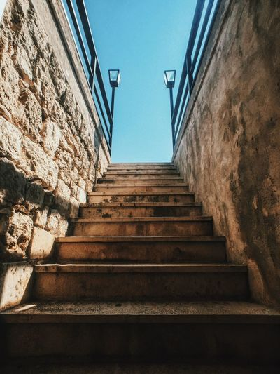 Steps amidst walls against sky
