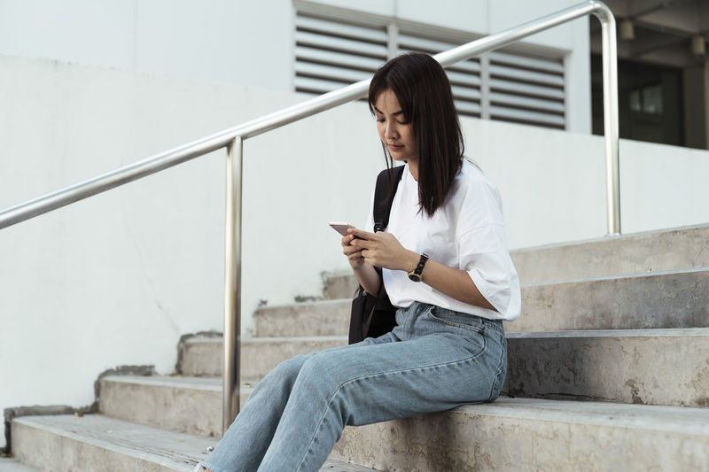 Young woman using mobile phone while sitting on staircase