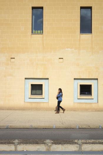 Side View Of Woman Walking On Sidewalk By Building