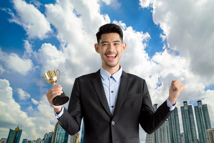 Achievement AWARD Business Businessman Cheerful Cloud - Sky Day Food And Drink Happiness Holding Lifestyles Looking At Camera Low Angle View Men One Person Outdoors Portrait Sky Smiling Standing Success Waist Up Winning Young Adult Young Men