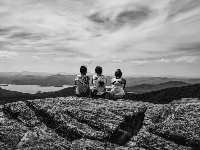 REAR VIEW OF FRIENDS SITTING ON MOUNTAIN AGAINST SKY