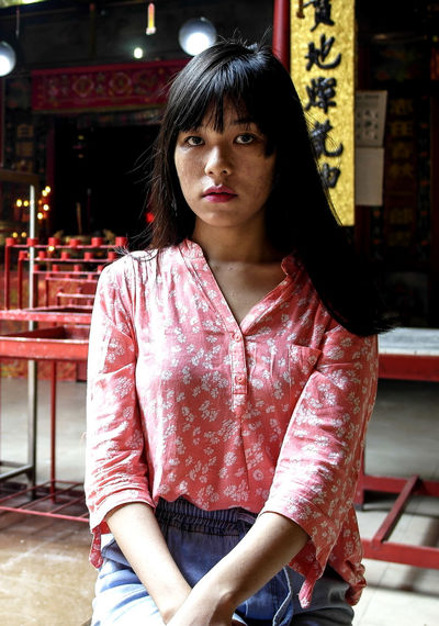 Portrait of young woman with bangs sitting in city