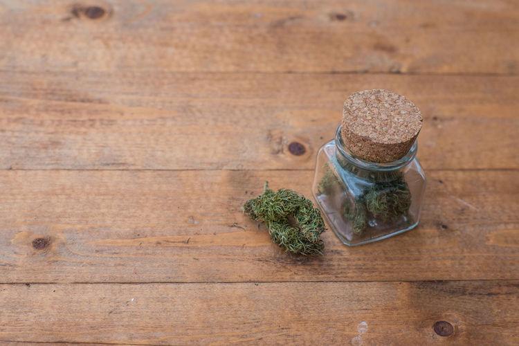 A jar of medical marijuana on a table Cancer Herb Lifestyle Natural Bushweed Cannabis, Close-up Glass - Material Health Jar Marijuana Medical Medicinal No People Sativa Strain Table Weed Wood - Material