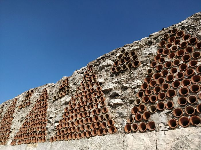 Low angle view of a patterned wall against the sky