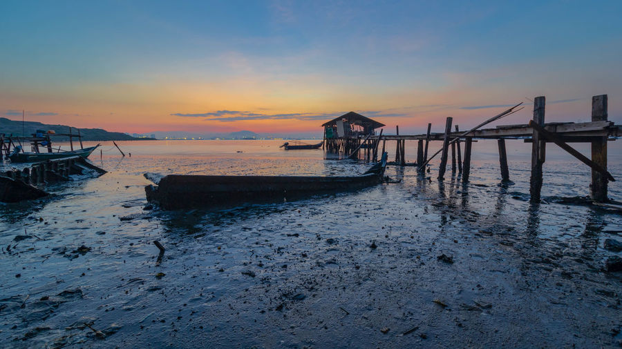 Water Sky Sunset Sea Built Structure Beach Architecture Scenics - Nature Tranquil Scene Beauty In Nature Tranquility Land Pier Nature Transportation No People Nautical Vessel Wood - Material Orange Color Post Wooden Post Outdoors