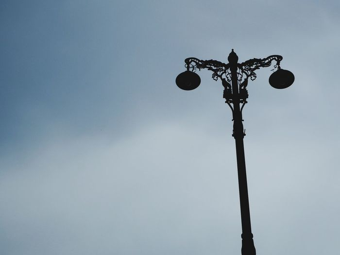 Low angle view of silhouette street light against blue sky
