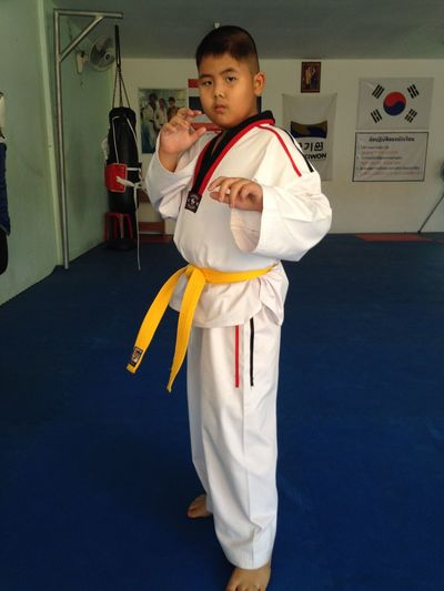 Portrait Of Boy In Karate Uniform Standing In Gym