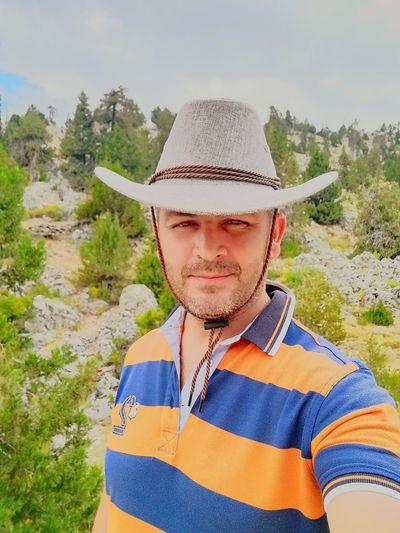 Portrait of man wearing hat against trees