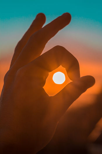 Close-up of hand holding sun during sunset