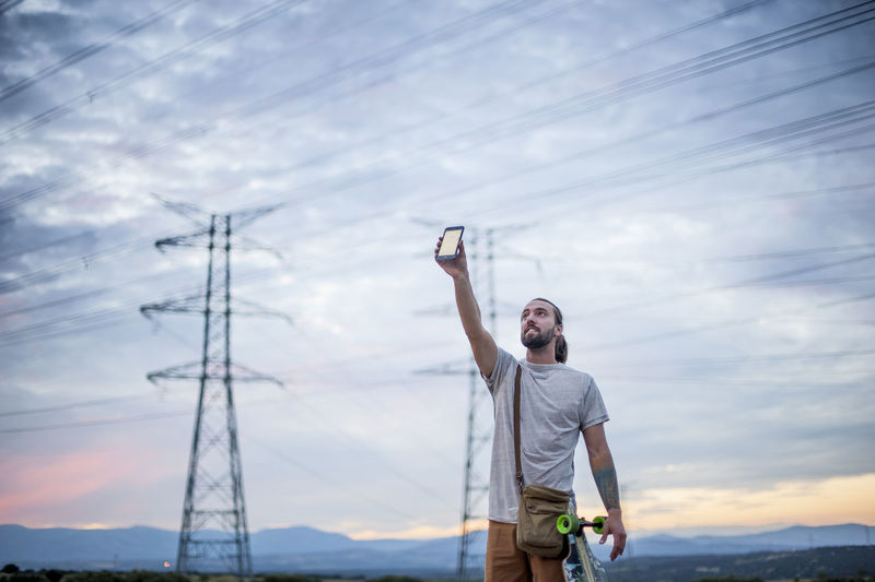 Low angle view of man standing on cable against sky