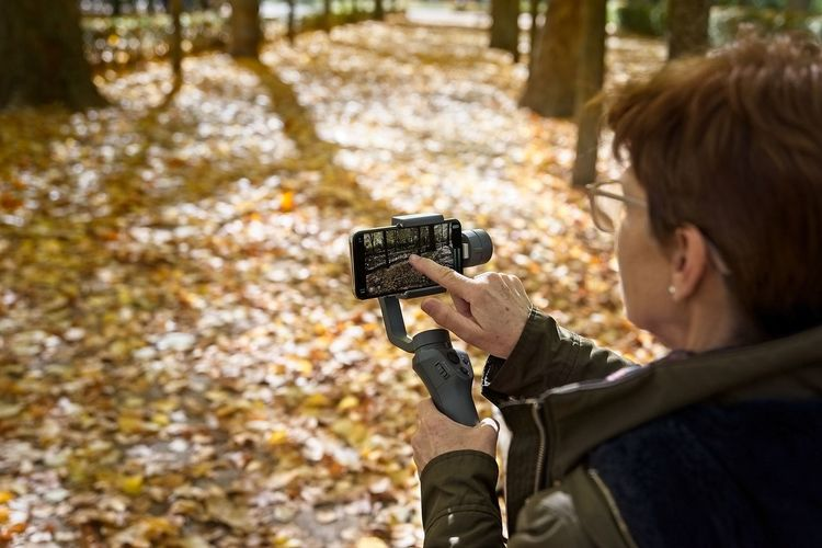 Senior woman drives her smartphone put on a gimbal to record video in a park in autumn Technology Photography Themes One Person Camera - Photographic Equipment Holding Headshot Tree Adult Nature Forest Activity Portrait Over The Shoulder View Target Shooting Aiming Communication Smart Phone Mobile Phone Gimbal Senior Adult Woman Autumn Leaves Photos Taking Pictures
