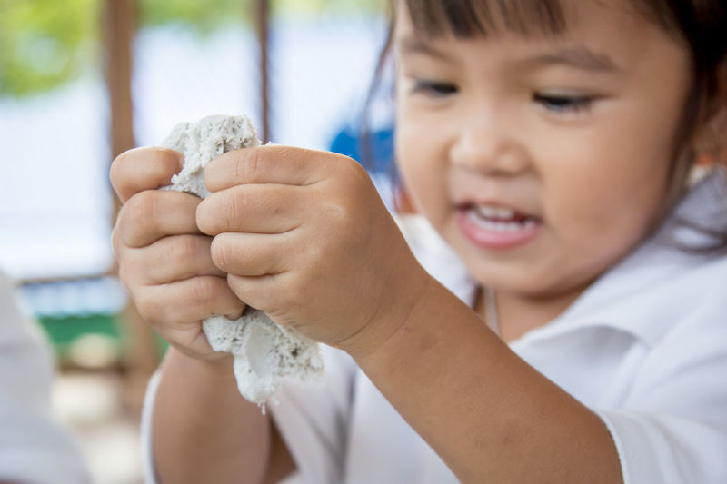 Close-Up Of Girl Playing With Clay