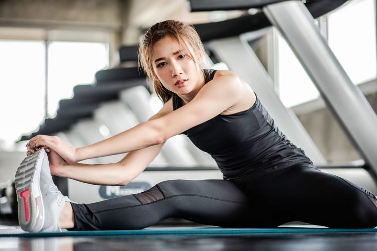 Portrait of young woman exercising while sitting in gym
