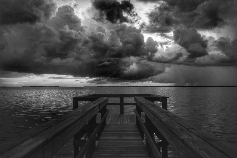 Pier On Sea Against Cloudy Sky