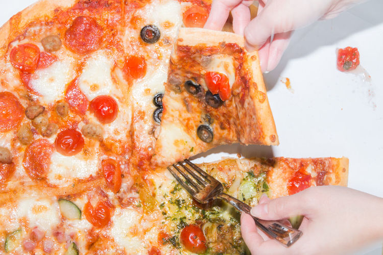 Cropped image of hand holding pizza on table