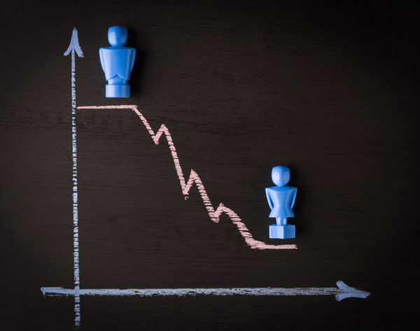 Wage gap and gender equality concept depicted with male and female figurines and hand drawn chalkboard line graph Concept Conceptual Conceptual Photography  Copy Space Female Figure Gender Equality Gender Gap Graph Human Representation Line Graph Male Wage Gap