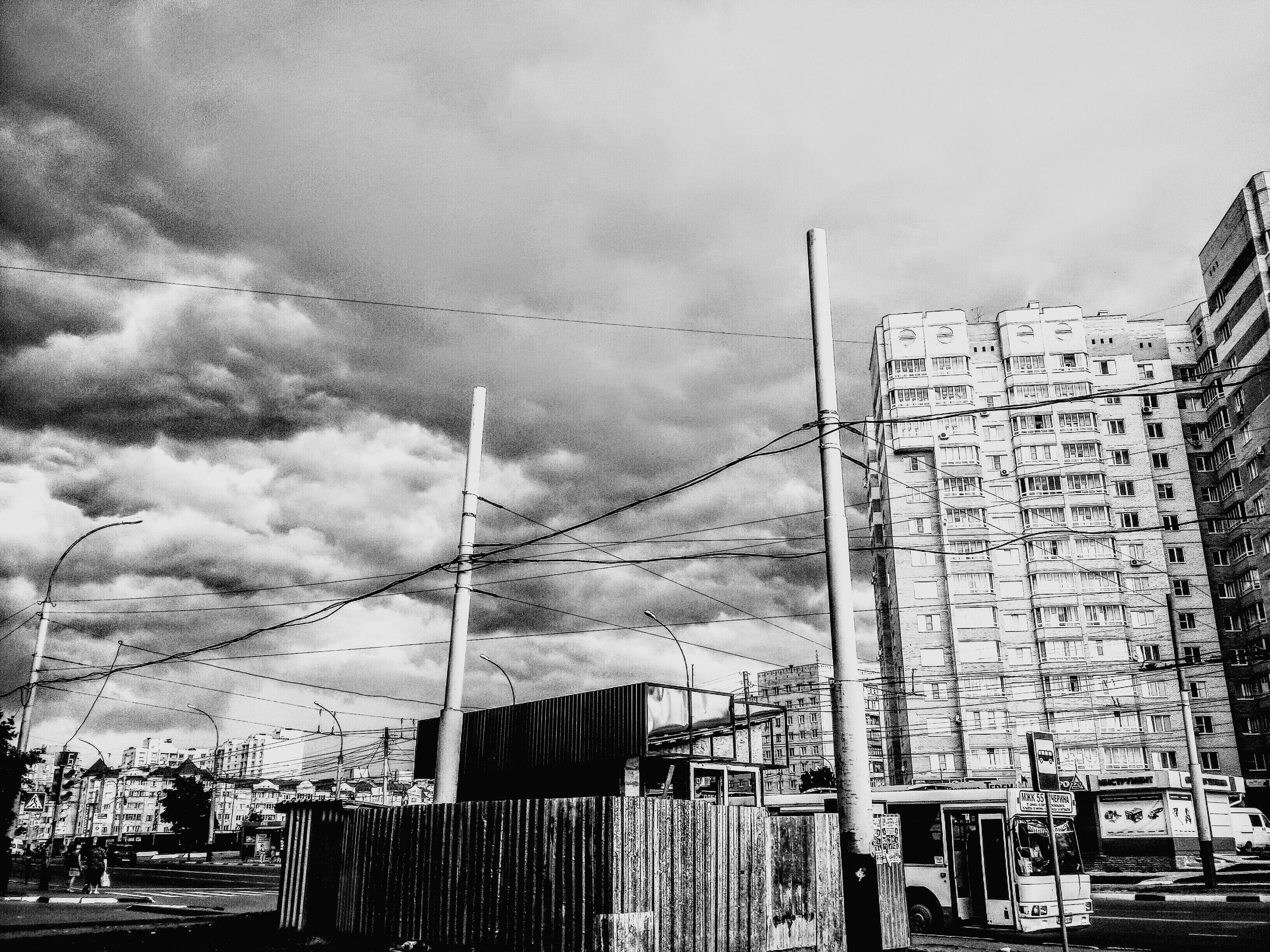 built structure, architecture, building exterior, sky, cable, power line, cloud, day, fence, outdoors, power supply, cloud - sky, high section, tall - high, development, no people