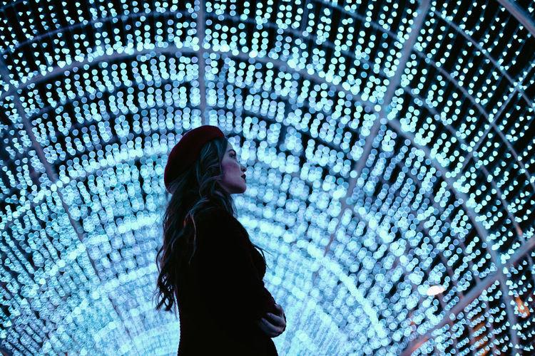 Side view of woman looking at illuminated corridor