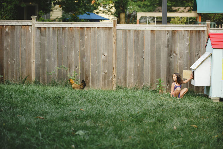 Woman sitting on grassy field by fence
