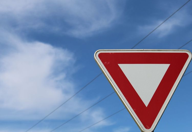 Low angle view of yield sign against sky