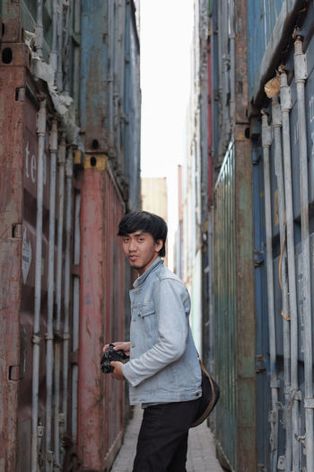 Portrait of man holding camera standing on alley amidst cargo containers