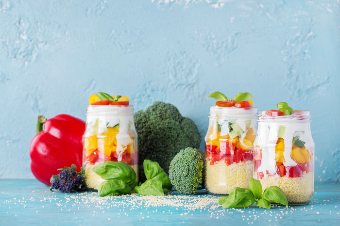 Cous cous with vegetables: bell pepper, cucumber, cherry tomatoes and yogurt in mason jar on blue background Backgrounds Basil Blue Brocolli Cauliflower Cherry Cous Cous Food Food And Drink Glass Greens Healthy Healthy Eating Healthy Food Jar Mason Pepper Salad Tomatoes Yogurt