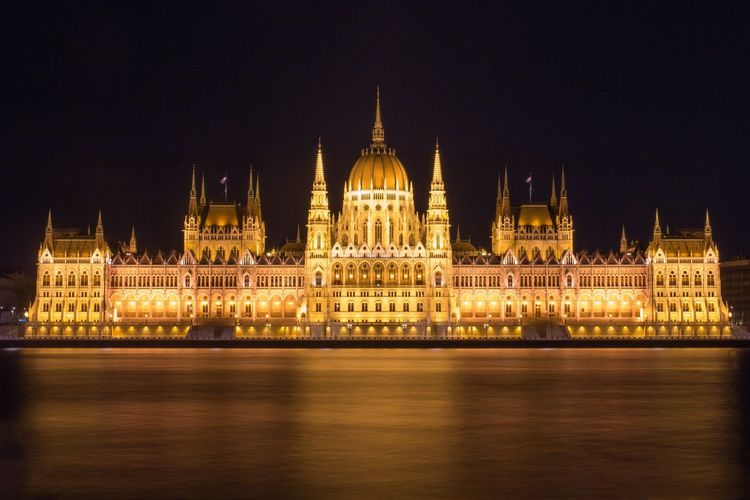 Illuminated hungarian parliament building by danube river against sky at night