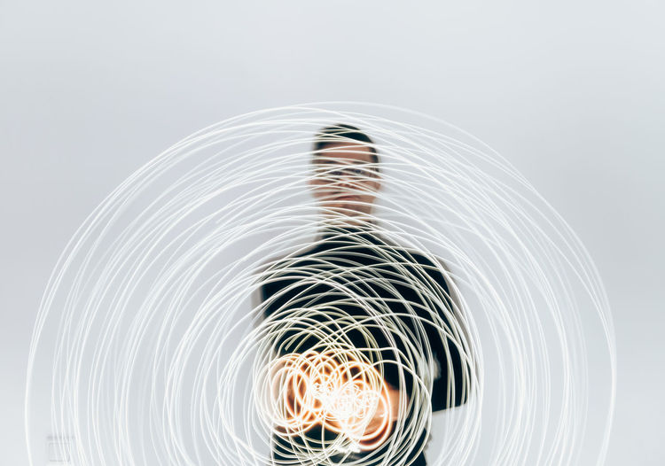 Man With Light Painting Against White Background