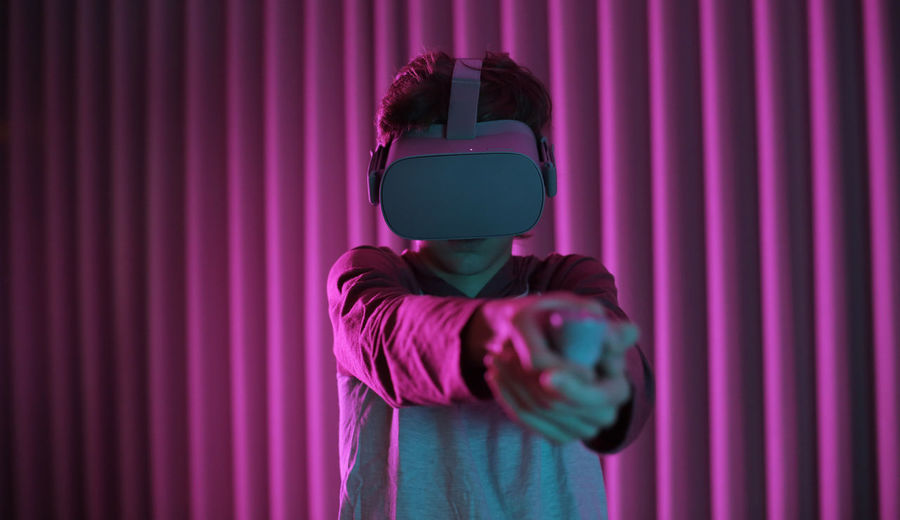 Boy wearing virtual reality simulators while standing against wall
