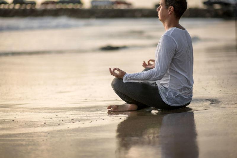 Full length of man meditating while sitting at beach