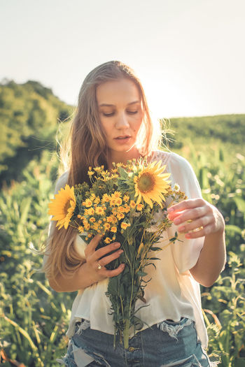 Woman holding flowers while standing against sky