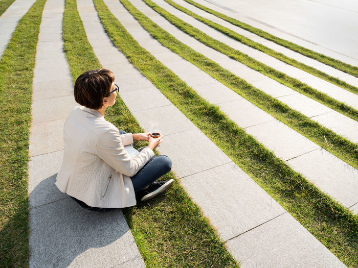 High angle view of woman using phone while sitting on grass
