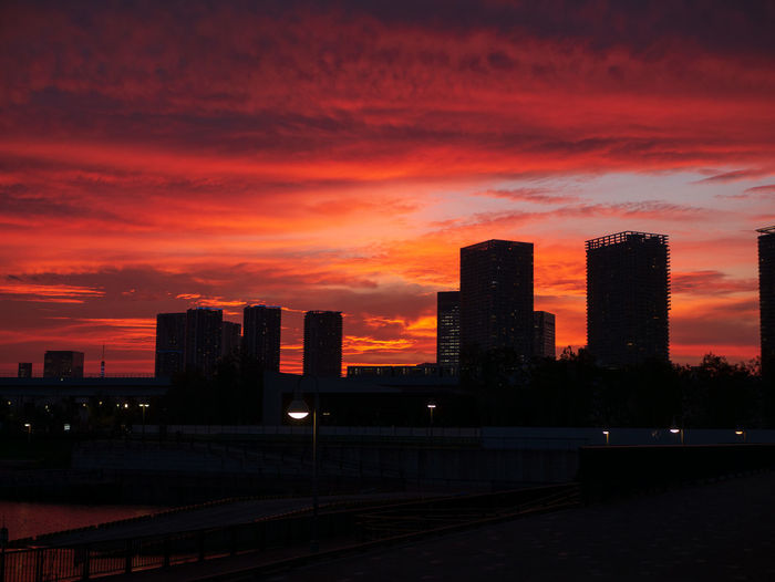 Silhouette buildings in city against romantic sky at sunset