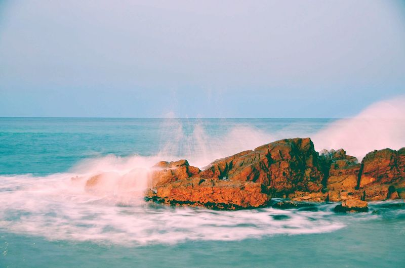 Scenic view of waves crashing on rocks against sky