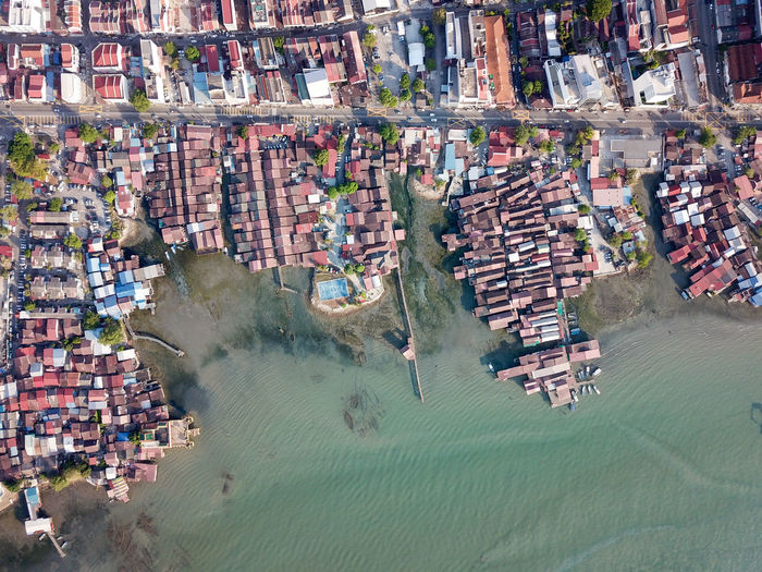High angle view of buildings by sea in city