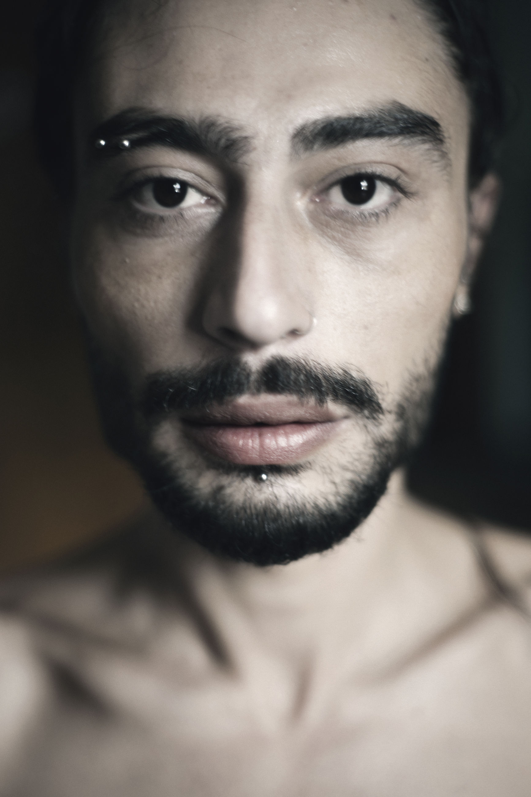 portrait, headshot, looking at camera, front view, one person, young adult, real people, indoors, close-up, young men, beard, lifestyles, facial hair, mid adult, focus on foreground, men, shirtless, mid adult men, human face, contemplation, black background