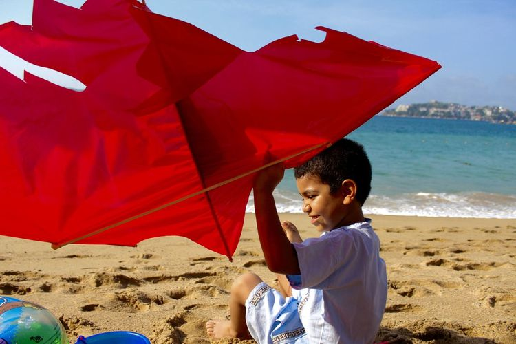 Boy playing with red kite at beach during sunny day