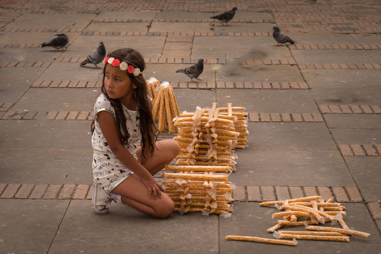 A girl selling corn as food for the many pigeons in front of the Cathedral of Bogotá , Plaza de Bolívar Bogotá Colombia Plaza De Bolivar Street Vendor Corn One Person Pigeon Pigeon Food