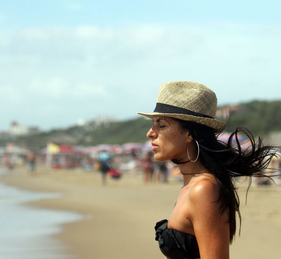 Woman in hat standing at beach against sky