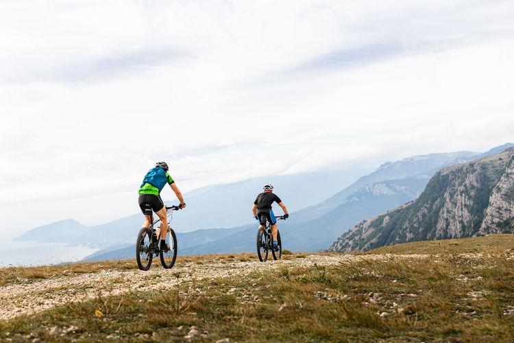 Two male cyclists biking on mountain road