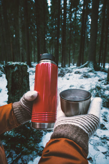 Cropped hands of woman having drink against trees in forest during winter