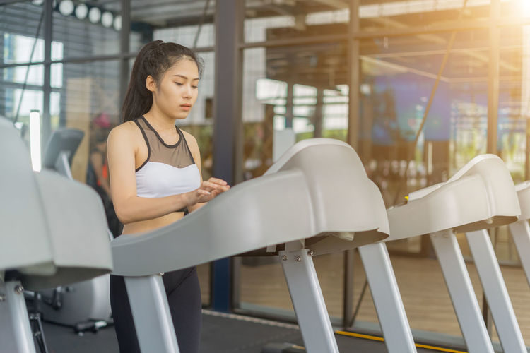 Young woman running on treadmill at gym