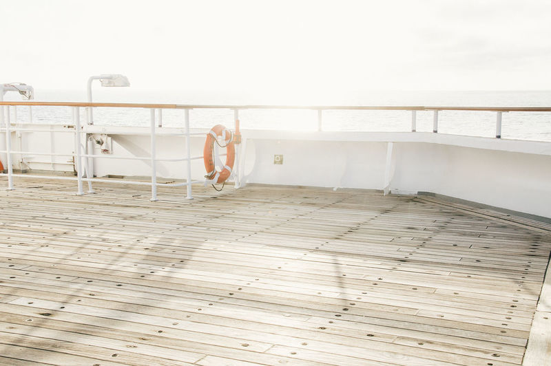 Empty boat deck with railings against clear sea