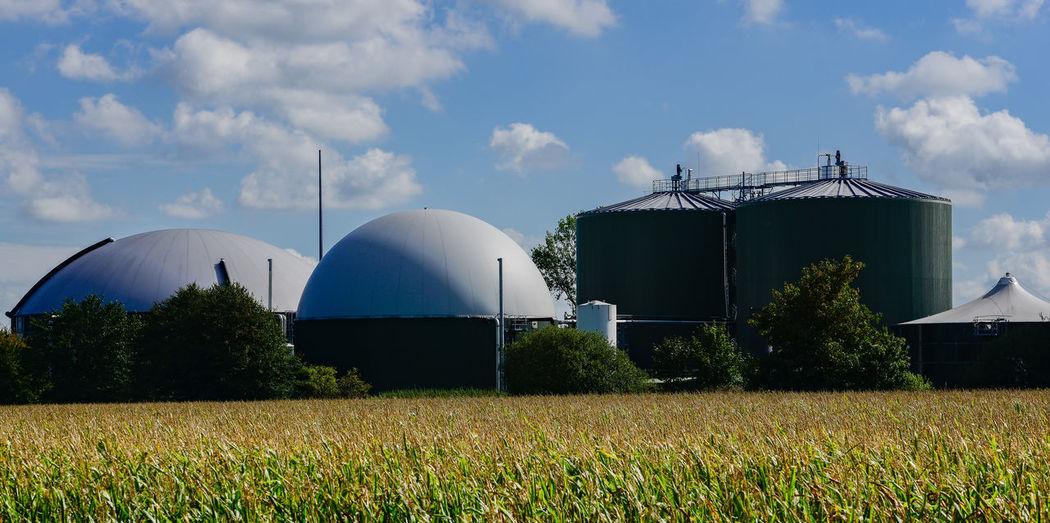 Industry on field against sky