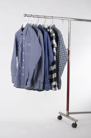 Shirts hanging on metallic rack against white background