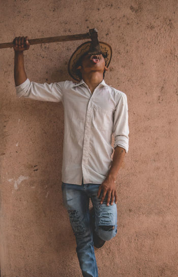 Teenage boy wearing hat holding axe while standing against wall