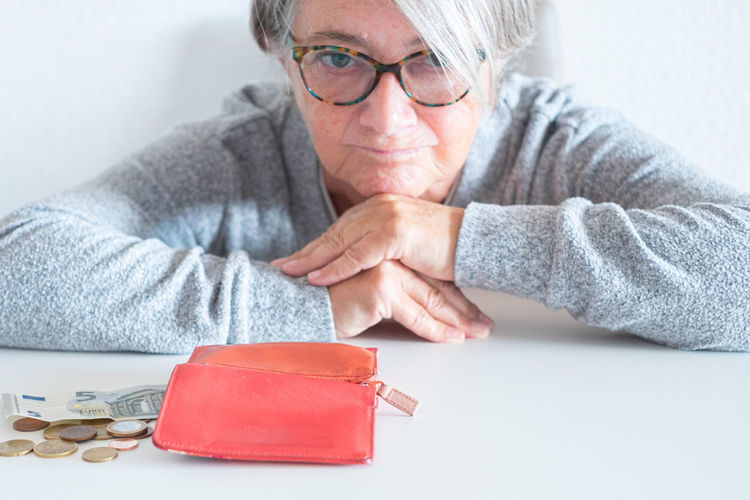 Sad woman with purse at table