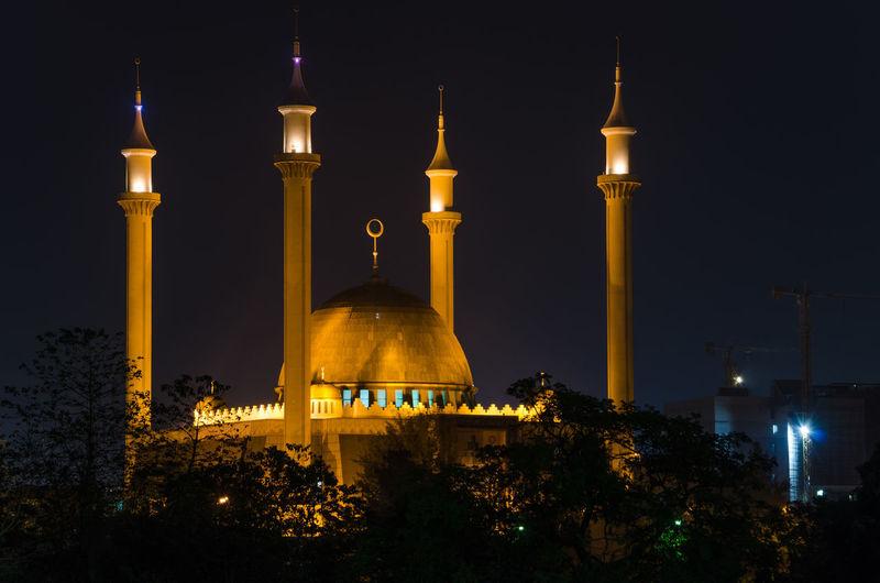 Illuminated national mosque of nigeria against sky at night