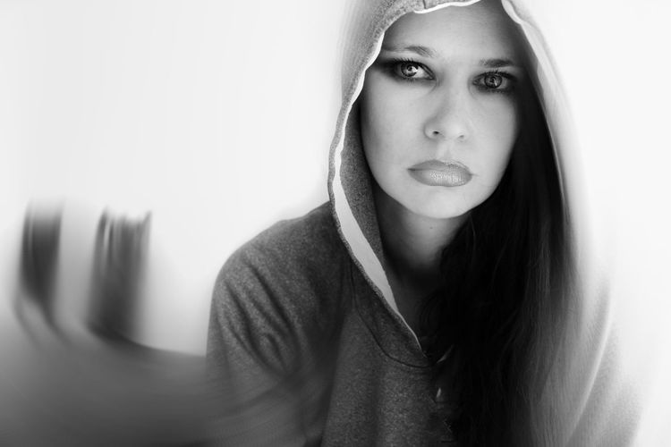 Portrait Of Woman Wearing Hooded Shirt Against White Background