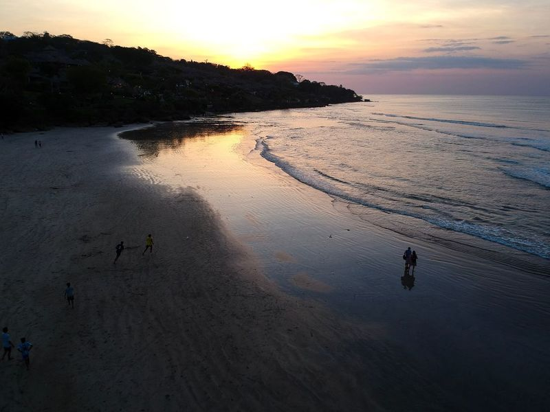Dusk: Jimbaran Beach, Bali. Bali Drone Photography Dusk Sunset In Paradise Travel Destinations Exploring Jimbaran Beach Jimbaran Bali Island Life Tropical Island Paradise Worlds Best Sunsets Sunset Nature Water Beach Beauty In Nature Scenics Real People Outdoors Tranquility Sea Sky Sand Leisure Activity High Angle View Tranquil Scene Reflection Lifestyles Silhouette An Eye For Travel